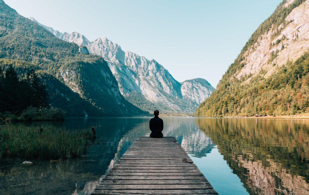 lac montagne paysage voyages homme de dos nature eau etude sur le manque de voyage tour mag